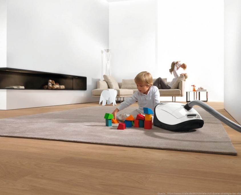 Staubsauger auf Teppich mit Kind